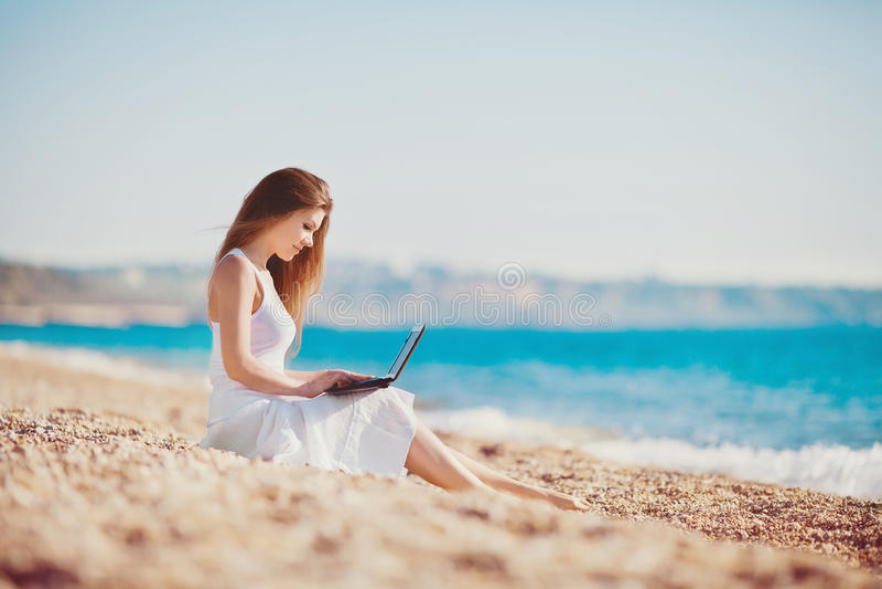 Gullig kvinna med den vita bärbara datorn på sommarstranden arkivfoto