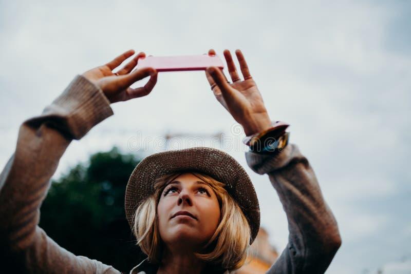 Gullig kvinna med en hatt som tar en bild med en mobiltelefon i gatan arkivfoto