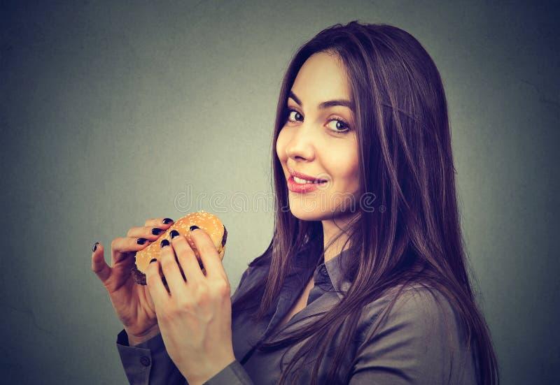 Gullig kvinna med en ostburgare som ser kameran arkivbild