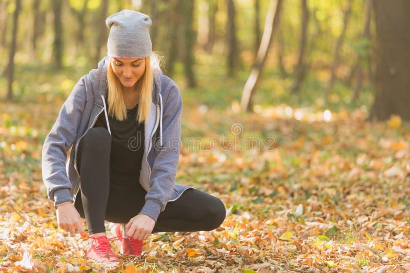 Gullig kvinna som binder hennes skor, innan att jogga arkivfoton