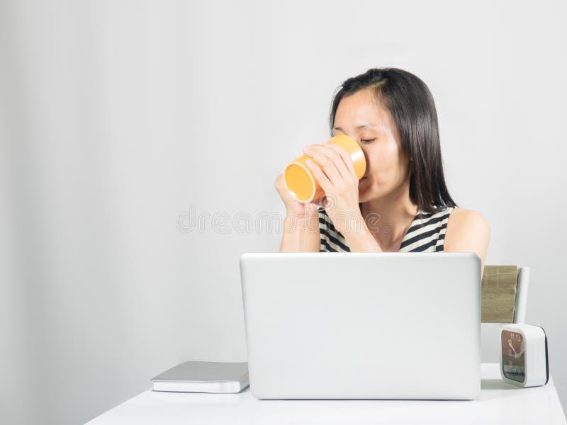 Gullig kvinna som dricker drycken på arbetsskrivbordet arkivbilder