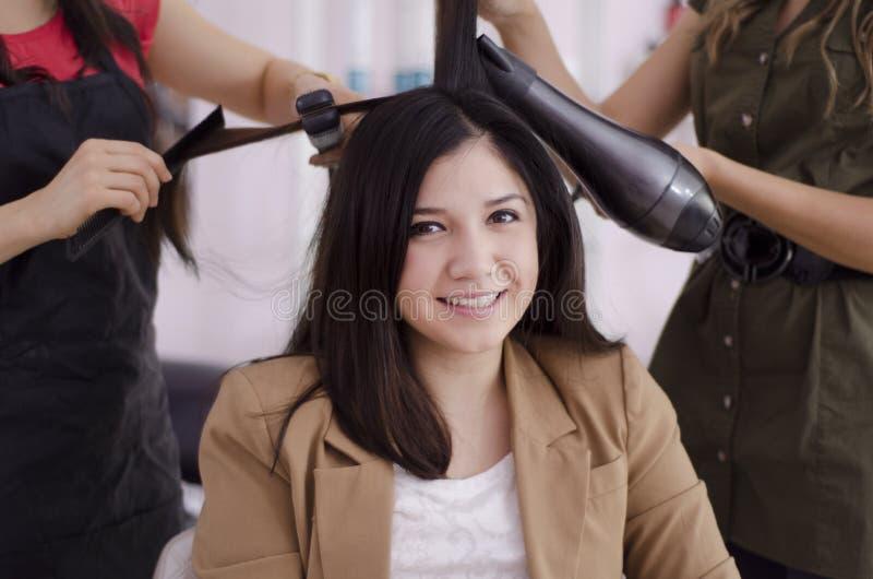 Gullig kvinna som får henne hår gjort royaltyfri fotografi