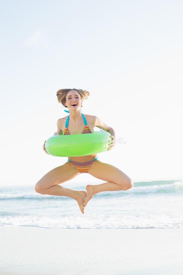Gullig kvinna som rymmer en rubber cirkel, medan hoppa på stranden arkivbilder