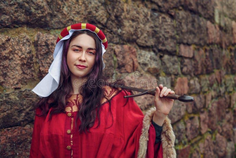 Gullig kvinna som rymmer ett svärd på hennes skuldra som lutar hennes skuldra på väggen royaltyfria bilder