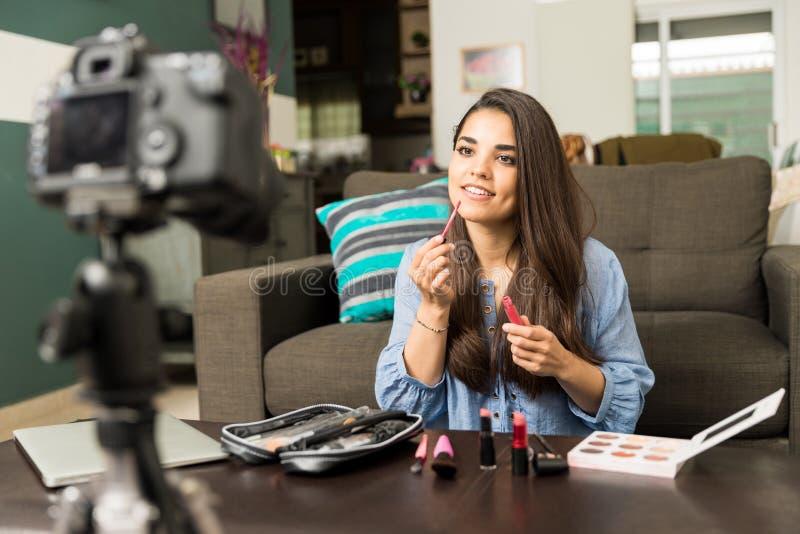 Gullig kvinna som sätter någon kantglans på videoen fotografering för bildbyråer