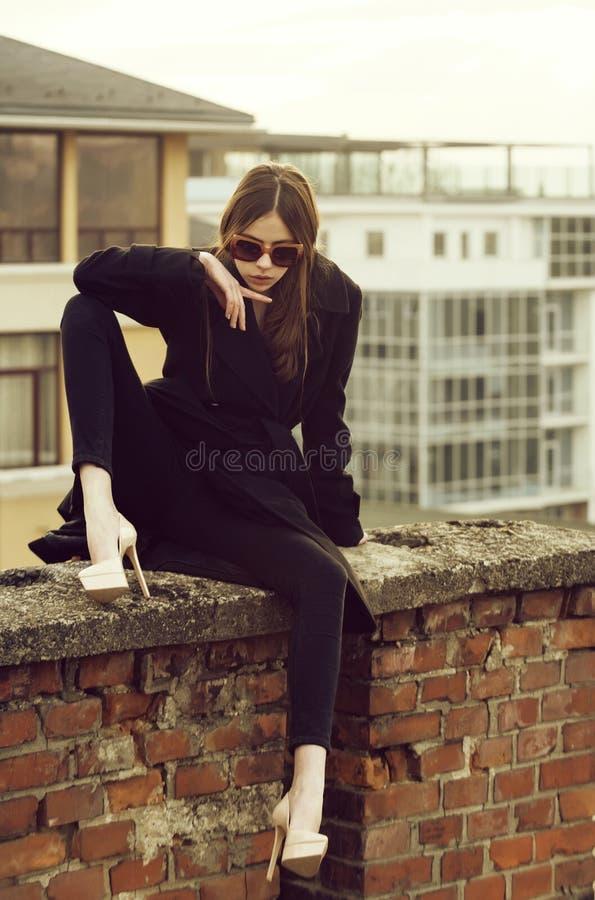Gullig kvinna som sitter på staketet för röd tegelsten arkivbild