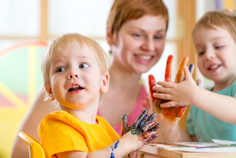 Gullig kvinna som spelar och målar med barn arkivfoto