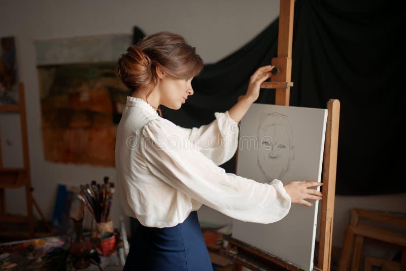 Gullig kvinnlig konstnärteckning i studio royaltyfria foton