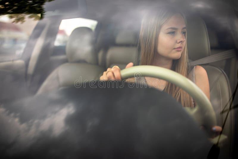 Gullig kvinnlig tonårig chaufför som tycker om hennes nytt fångna körningslicens arkivfoto