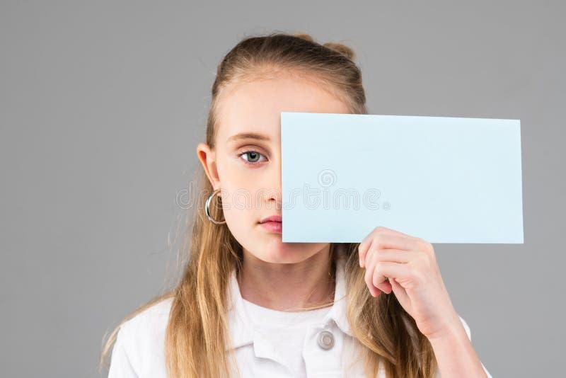 Gullig långhårig liten dam med blåa ögon som rymmer tomt papper royaltyfri bild