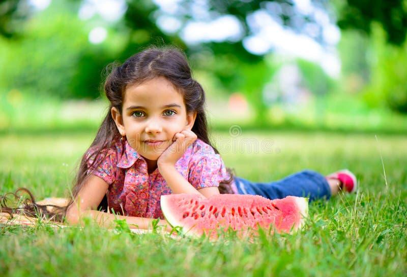 Gullig latinamerikansk flicka som äter vattenmelon royaltyfria bilder