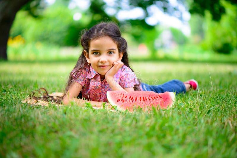 Gullig latinamerikansk flicka som äter vattenmelon arkivbild
