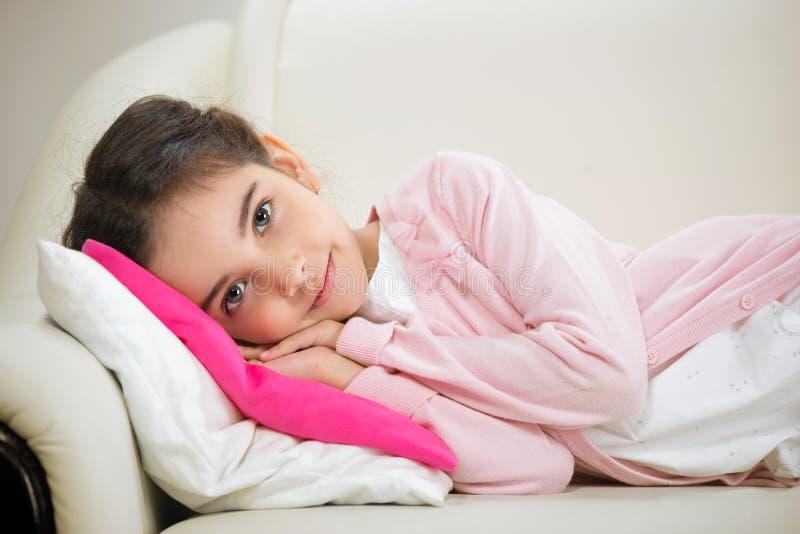 Gullig latinamerikansk flicka som ligger i säng royaltyfri fotografi