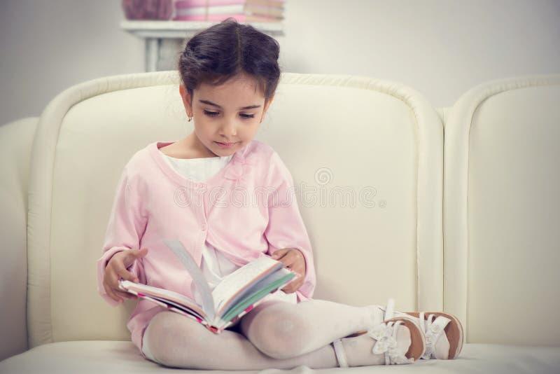 Gullig latinamerikansk liten flickaläsebok på soffan royaltyfria bilder