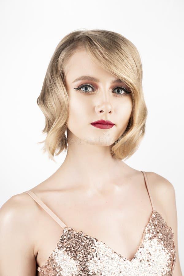 Gullig le blond flicka med stora h?rliga ?gon, r?da kanter och tappningstilfrisyr som b?r en guld- mousserande kl?nning isolerat arkivbilder