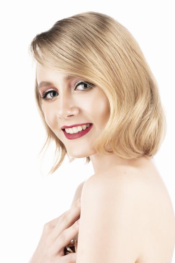 Gullig le blond flicka med stora h?rliga ?gon, r?da kanter och tappningstilfrisyr som b?r en guld- mousserande kl?nning isolerat arkivfoto