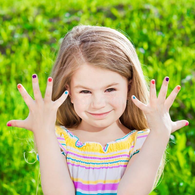Gullig le blond liten flicka med många-färgad manikyr royaltyfri bild
