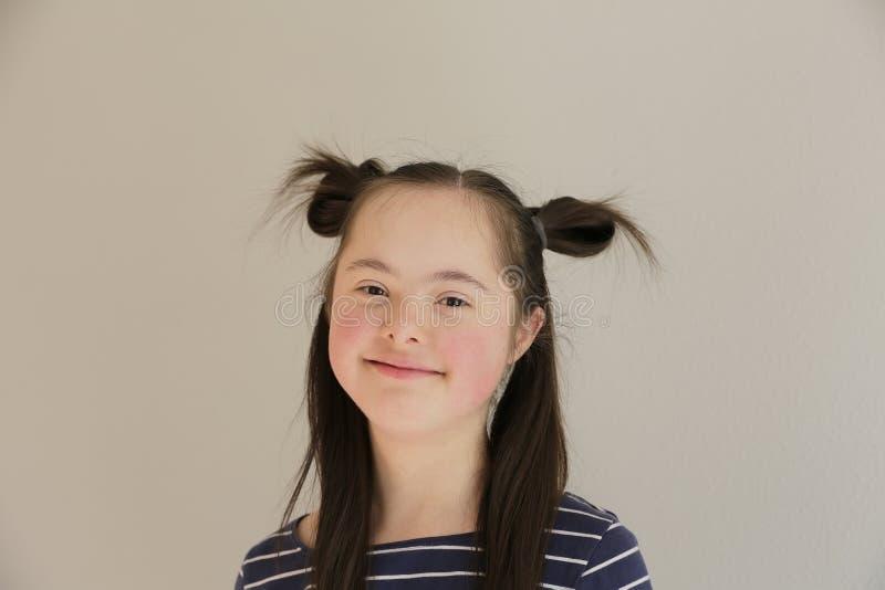 Gullig le Down Syndrome flicka på den gråa bakgrunden arkivfoto