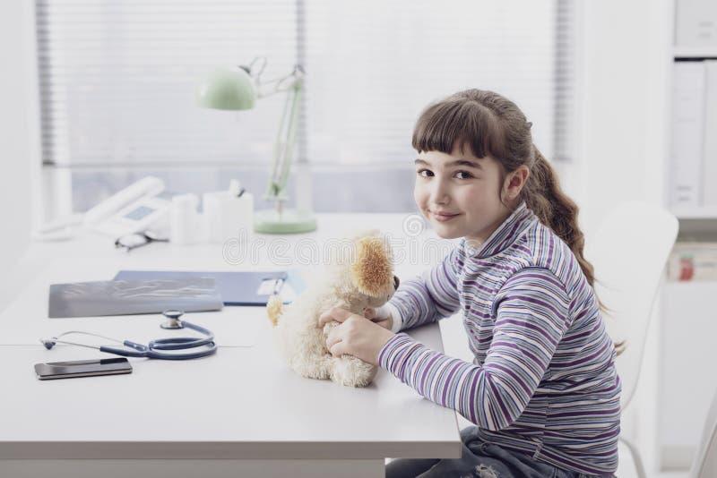 Gullig le flicka i doktorns kontor fotografering för bildbyråer