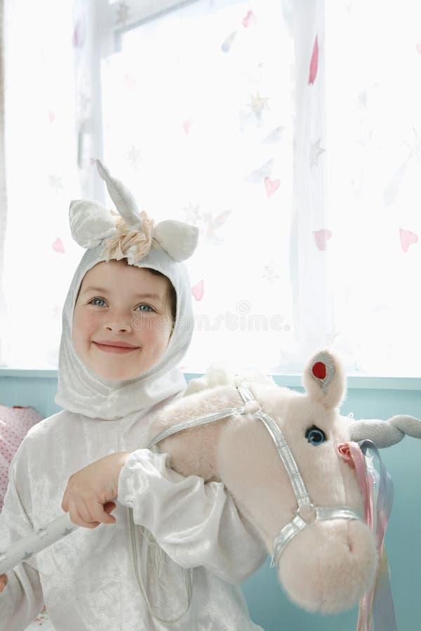 Gullig le flicka i Unicorn Costume With Toy Horse royaltyfri fotografi