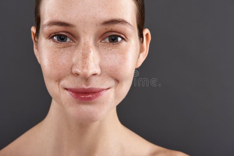 Gullig le flicka med fräknar som står mot grå bakgrund fotografering för bildbyråer