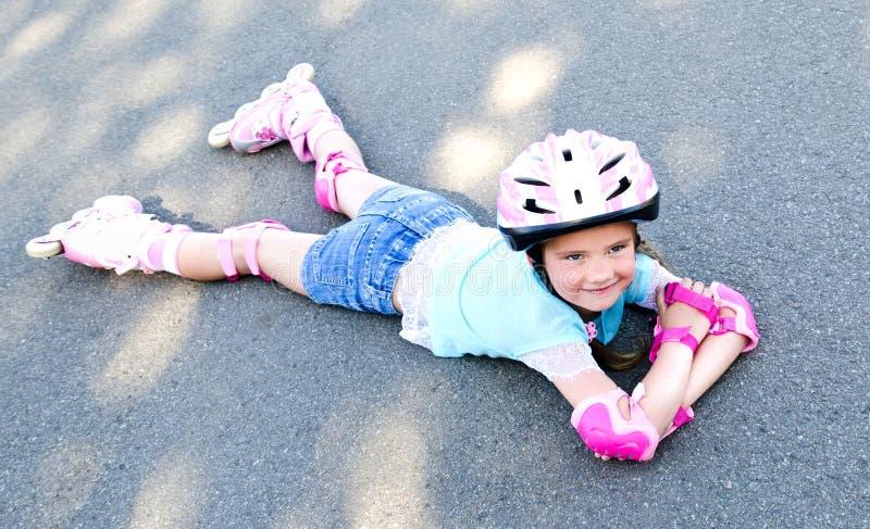 Gullig le liten flicka i rosa rullskridskor arkivfoto