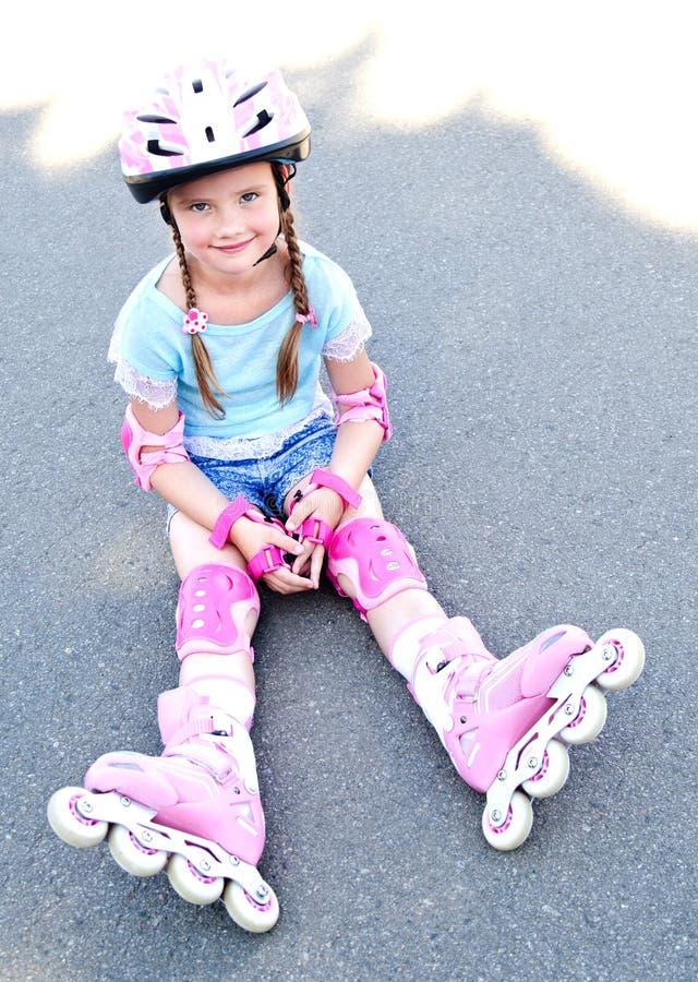 Gullig le liten flicka i rosa rullskridskor royaltyfria bilder
