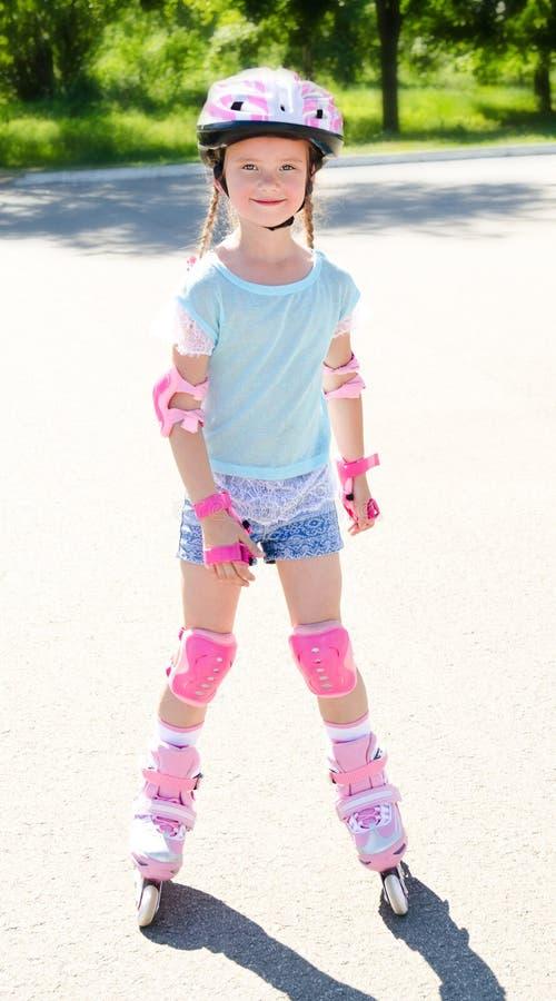 Gullig le liten flicka i rosa rullskridskor royaltyfri fotografi