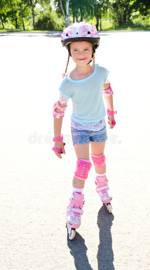 Gullig le liten flicka i rosa rullskridskor arkivfoton
