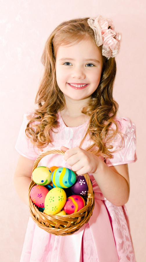 Gullig le liten flicka med korgen som är full av det färgrika easter ägget arkivbild