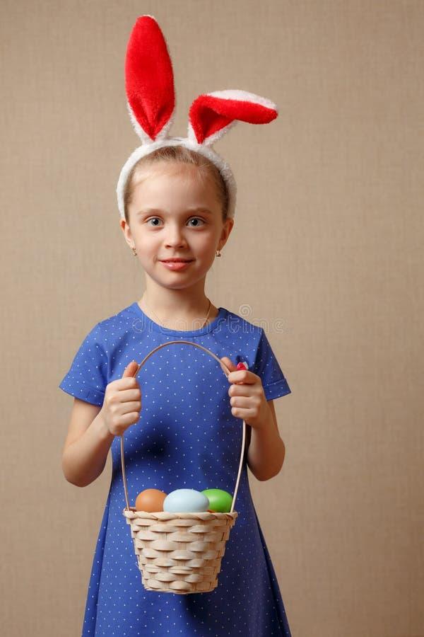 Gullig le liten flicka med korgen som är full av färgrika easter ägg arkivfoto