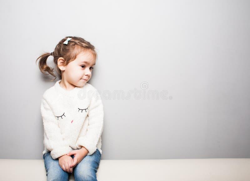 Gullig le liten flicka på grå bakgrund arkivbilder