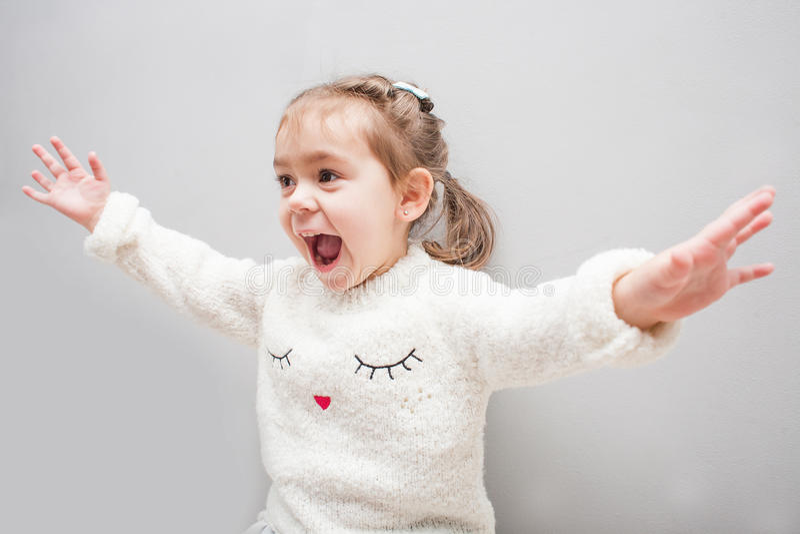 Gullig le liten flicka på grå bakgrund royaltyfri foto