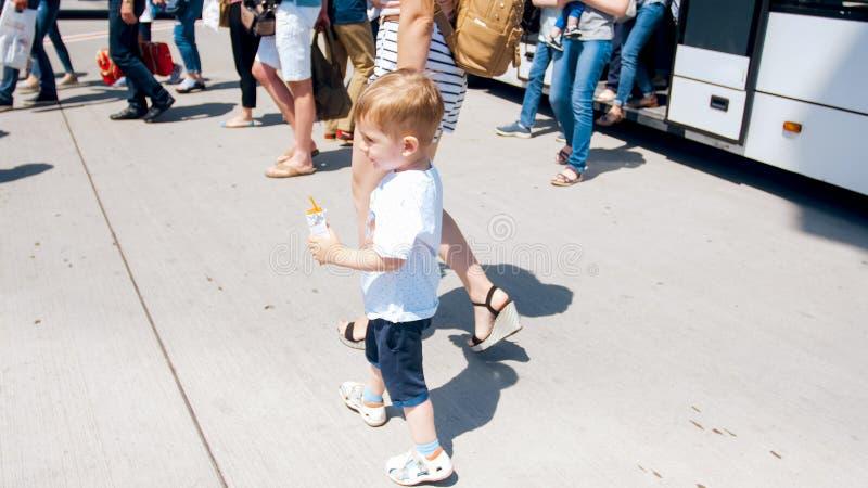 Gullig le moder för litet barnpojkeinnehav vid handen och gå ut ur bussen på flygplatslandningsbana royaltyfri bild