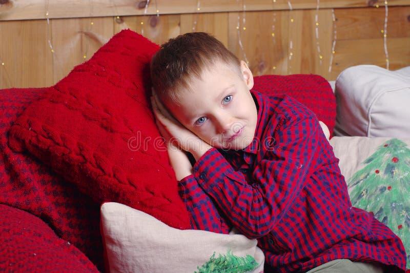 Gullig le pojke som ligger på en röd stucken kudde julen dekorerar nya home idéer för garnering till royaltyfri bild