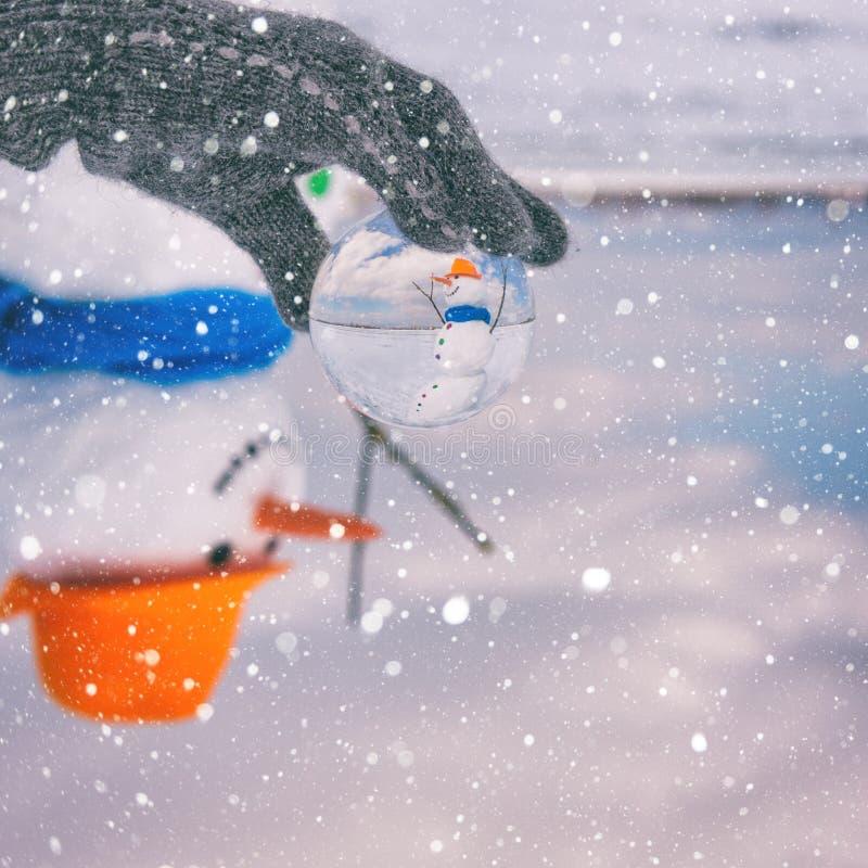 Gullig le snögubbe i exponeringsglasbollen, lycklig vinter, färgrik bakgrund med snöflingor arkivfoto