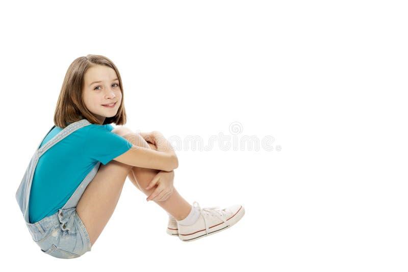 Gullig le tonårig flicka som sitter på golvet som isoleras på vit bakgrund royaltyfri fotografi