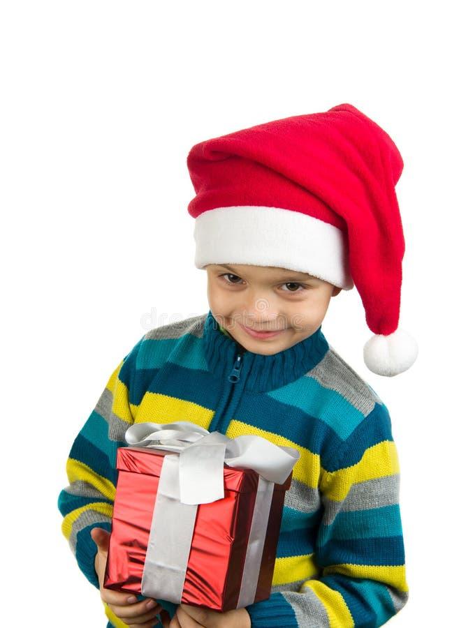 Gullig le unge med gåva och den santa hatten royaltyfri fotografi
