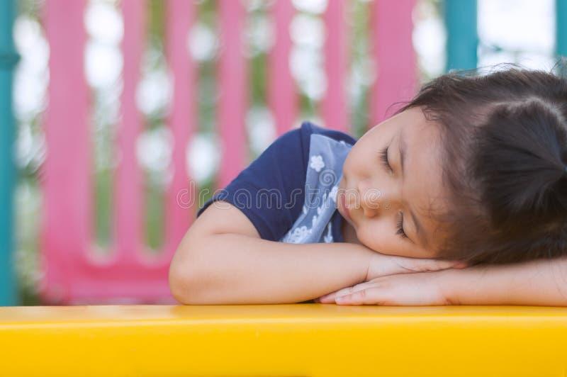 Gullig lite asiatisk flicka som sover i lekplatsen fotografering för bildbyråer