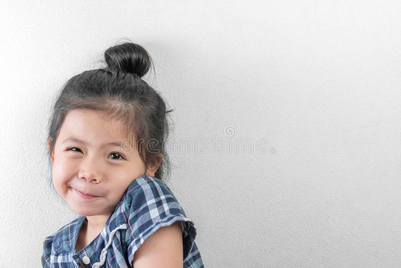 Gullig liten asiatisk flicka som ler på vit väggbakgrund royaltyfri bild
