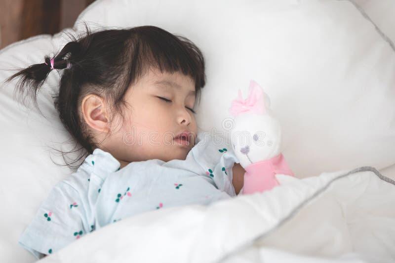 Gullig liten asiatisk flicka som sover med dockan i säng arkivfoton