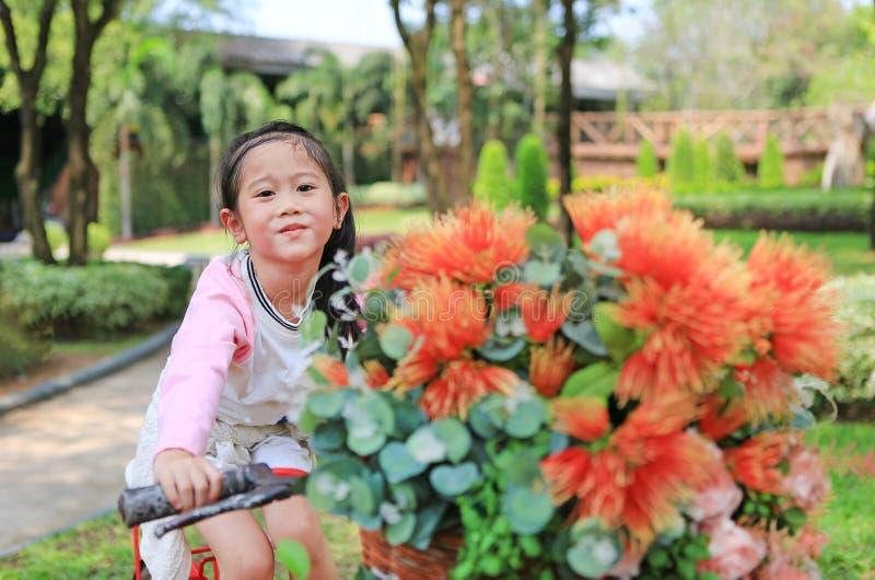 Gullig liten asiatisk flickaridning på cykeln med korgen av blomman på trädgården royaltyfri bild