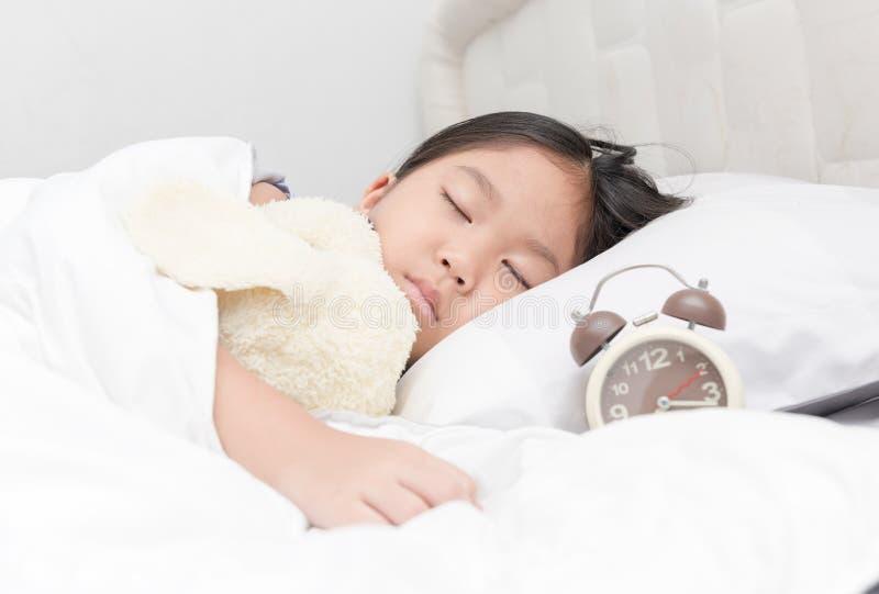 Gullig liten asiatisk flickasömn- och kramdocka på säng royaltyfria foton