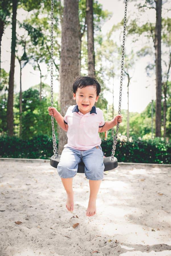 Gullig liten asiatisk pojke i en parkera på en trevlig dag utomhus royaltyfri bild