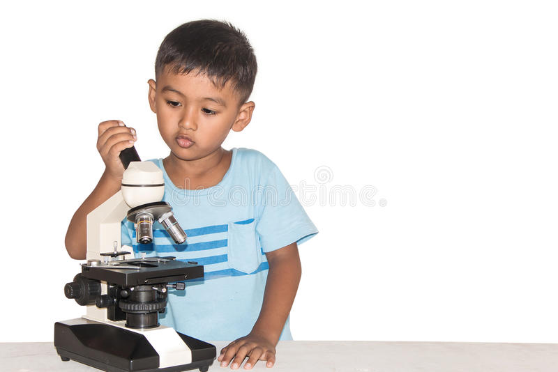 Gullig liten asiatisk pojke och mikroskop arkivbilder