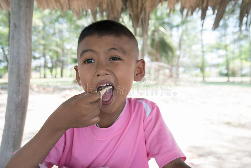 Gullig liten asiatisk pojke som äter mellanmålet arkivfoton