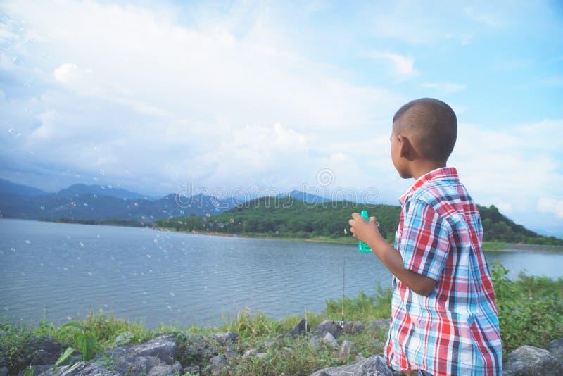 Gullig liten asiatisk pojke som blåser såpbubblan fotografering för bildbyråer