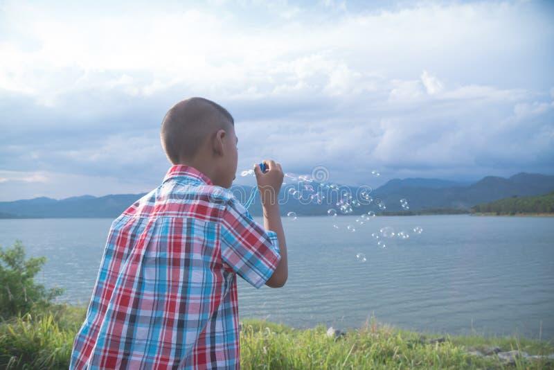 Gullig liten asiatisk pojke som blåser såpbubblan arkivfoton