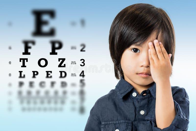 Gullig liten asiatisk pojke som gör visionprovet arkivbilder