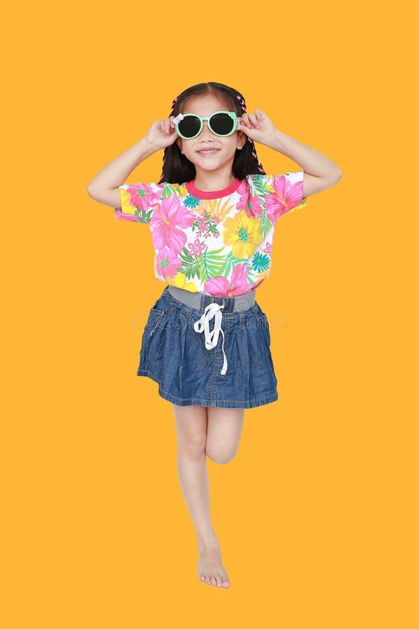 Gullig liten asiatisk ungeflicka som bär en blommasommarklänning och solglasögon som isoleras på gul bakgrund Sommar och modebegr royaltyfri foto